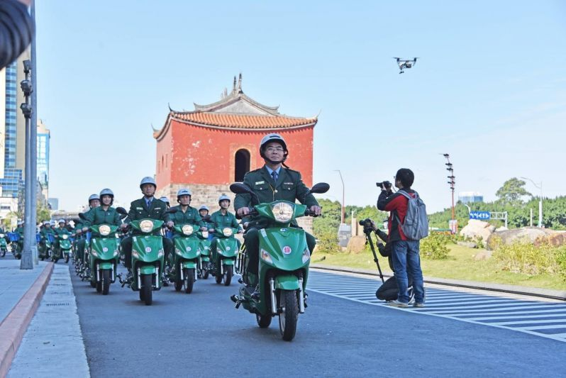 Chunghwa Post workers drive past Taipei City's historic North Gate Jan. 15 following a commissioning ceremony for a fleet of 1,627 e-scooters. (Courtesy of Chunghwa Post)