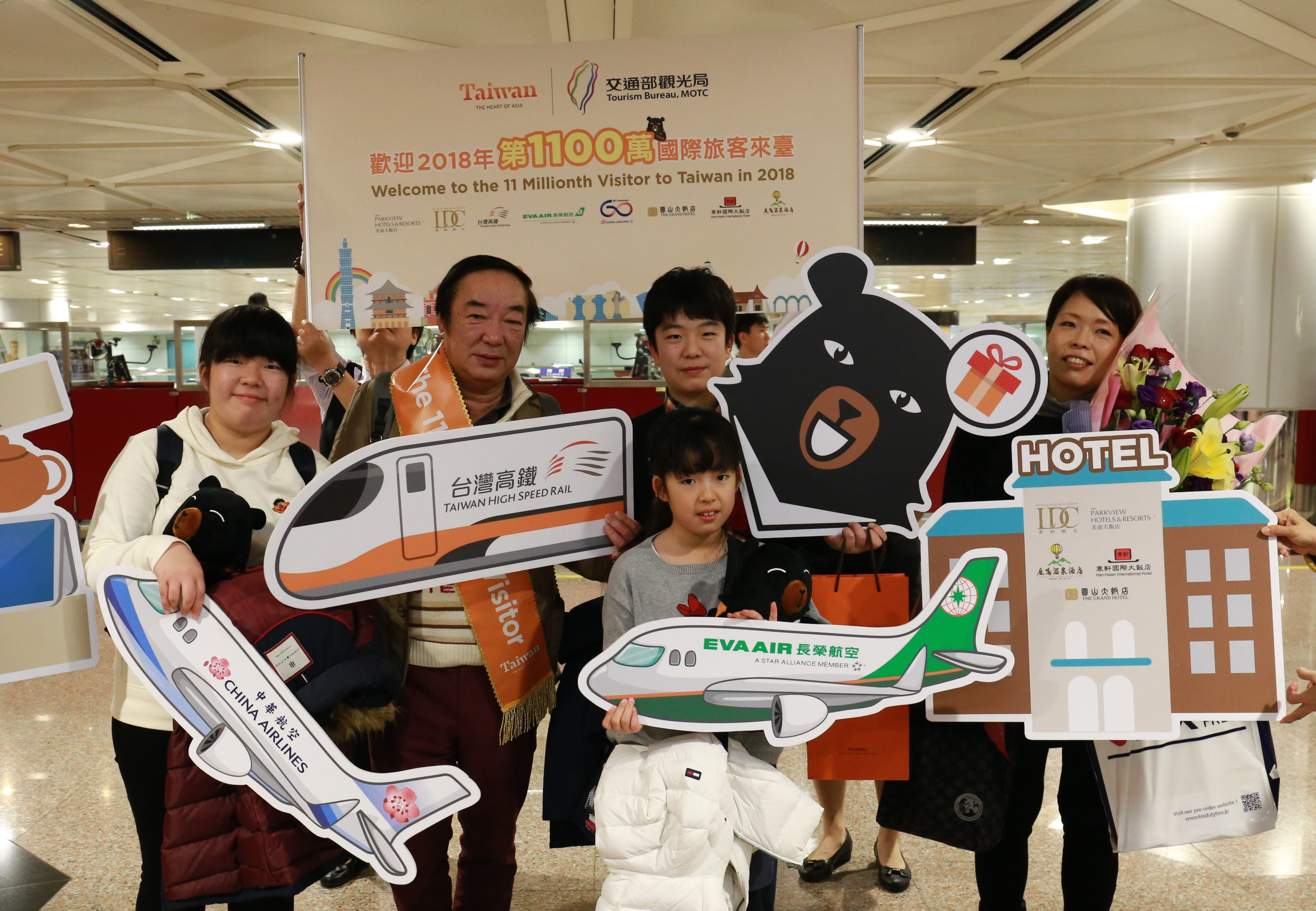 Taiwan's 11 millionth visitor of 2018 Shinobu Nishikawa (second left) and family members are all smiles Dec. 30 at Taiwan Taoyuan International Airport. (Courtesy of Tourism Bureau)